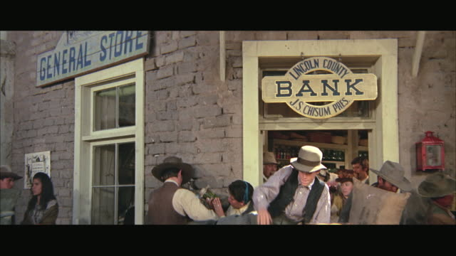 1970s CU ZO MS People walking in and out of bank, men carrying bags