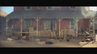 1970s WS Shootout in Western town, dead bodies lying in street by porch railing