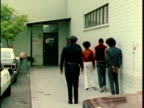 1970s WS ZI Teens being escorted into police station, Los Angles, California, USA, AUDIO