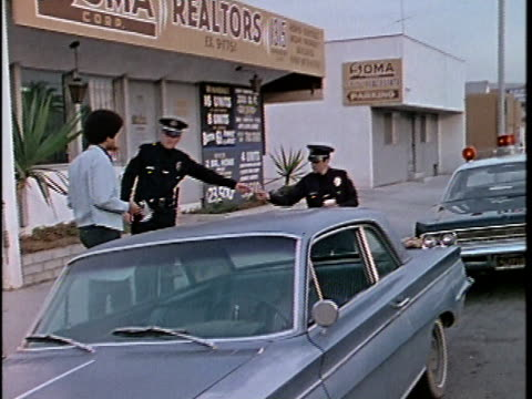 1970s WS Two police officers checking driver's license of teenage boy on street, Los Angeles, California, USA, AUDIO