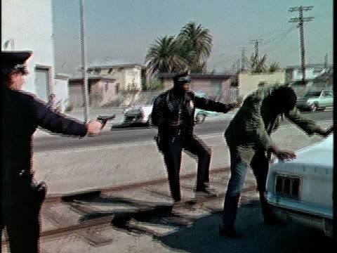 1970s MS DS Two police officers searching man on street at car, Los Angeles, California, USA, AUDIO