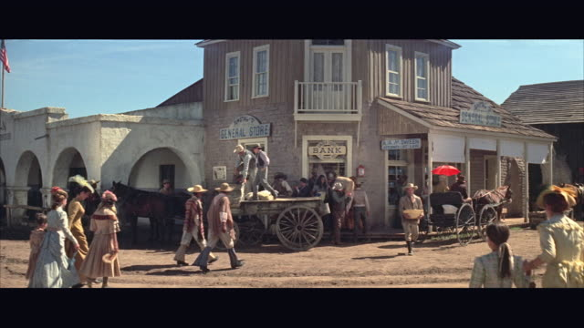 1970s WS Western town street activity, street bank and general store with people