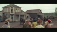 1970s WS Western town street activity, townspeople watching wagons and riders coming into town