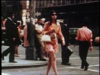 1970s zoom in woman in groovy dress + sunglasses carrying purse crossing NYC street / tilt down to feet