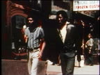 1970s zoom out two Black men walking on NYC sidewalk / one eating ice cream cone, one in leather jacket