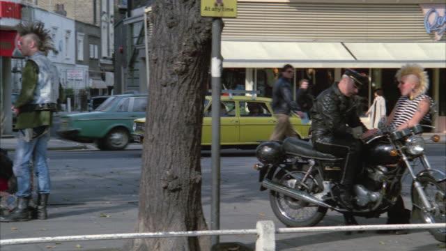 1980s WS PAN Car driving past punks gathered on sidewalk / London, UK