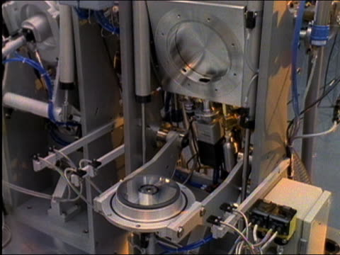 1980s high angle close up robotic machines manufacturing compact discs in factory