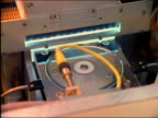 1980s high angle medium shot robotic machines manufacturing compact discs in factory