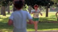1980s medium shot smiling woman race walking through park while wearing wrist weights / Houston