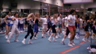 1980s medium shot zoom out men and women working out in aerobics class