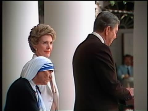 1980s Mother Teresa standing between Nancy Ronald Reagan giving speech / Washington DC