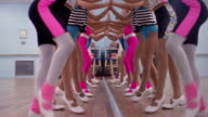 1980s slow motion low angle close up legs of girls tap dancing in a line with hands pressed to mirror / Dallas, Texas
