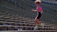 1980s slow motion medium shot tracking shot woman running up bleachers in stadium