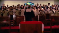 1980s wide shot zoom in gospel choir clapping and swaying + singing in church / director's back to CAM / Houston