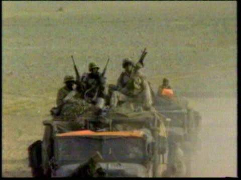 1Jan1991 MONTAGE Persian Gulf War Desert Storm US convoy in desert Hummers soldiers w/ heavy artillery full battle gear soldiers walking on road /...