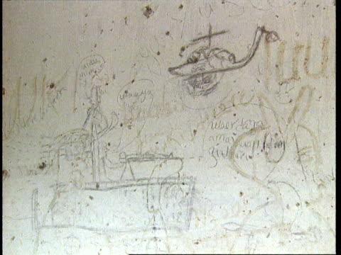1Oct1998 MONTAGE Graffiti drawings on wall full of bullet holes depicting militia firing guns and helicopter crashing / Mogadishu Benadir Somalia