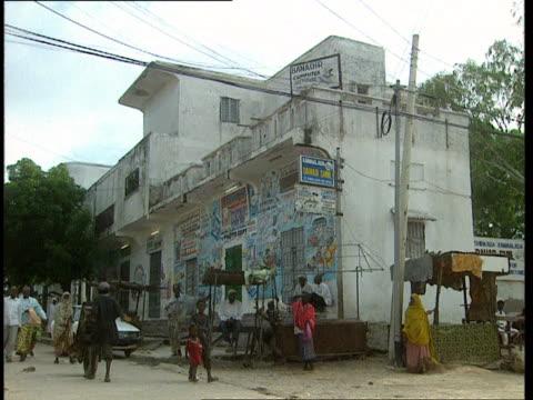 1Oct1998 WS Pedestrians walking in road past shops and businesses near US Army Rangers Black Hawk helicopter crash site / Mogadishu Benadir Somalia