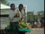 1Oct1998 MS Young man eating banana older man placing bananas on display cart for sale / Mogadishu Benadir Somalia