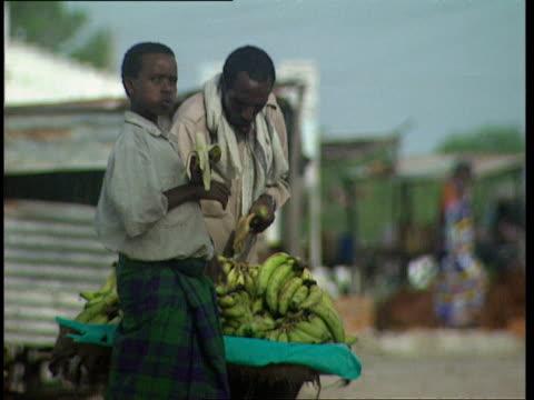 1Oct1998 MS Young man eating banana older man placing bananas on display cart for sale / Mogadishu Benadir Somalia