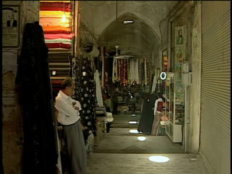1st Feb 2000 WS Alley of grand bazaar, man standing at kiosk in fabric district / Kashan, Iran