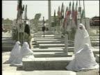 1st March 2000 WS Women in white veils sitting around grave in cemetery / Varzaneh, Ispahan, Iran