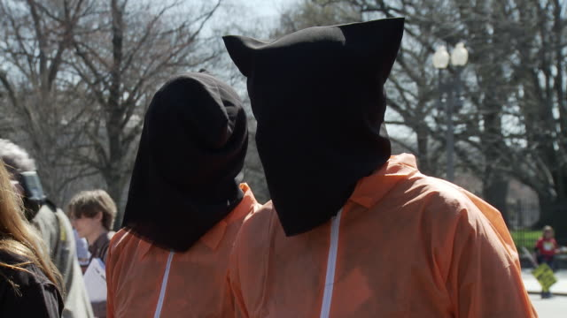20Mar2010 CU Two people with black hoods and orange jumpsuits dressed like Guantanamo Bay prisoners / Washington DC USA / AUDIO