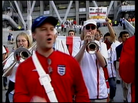 21Jun2002 MONTAGE England supporters band playing 'we'll meet again' as leaving stadium fans dressed up as David Seaman lookalikes / Shizuoka Japan /...