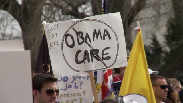 21Mar2010 CU Protestors holding sign reading Obama Care with circle and slash / Washington DC USA / AUDIO