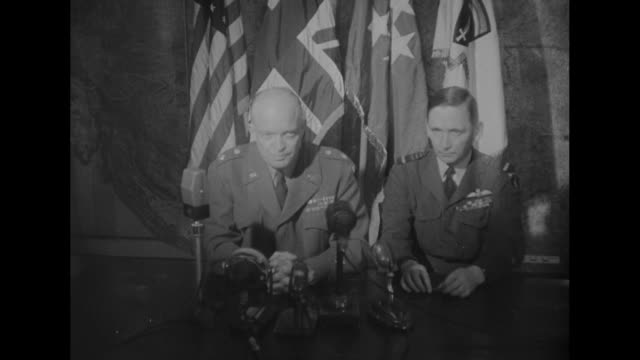 2shot RAF Air Marshal Sir Arthur Tedder and Gen Dwight Eisenhower sit in front of a bank of flags of Allied nations inside the headquarters of...