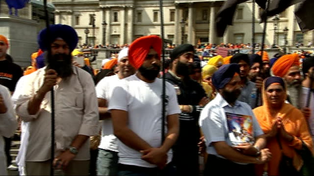 Sikhs demonstrate in Trafalgar Square ENGLAND London Trafalgar Square EXT Sikh demonstrators holding black flags and standing near to black coffins /...