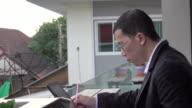 4k: Aziatische Man met behulp van digitale tablet schrijven nota boek