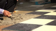 4k, construction worker using putty knife tiling floor