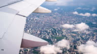 4k footage Aircraft wing flying through the clouds and Bangkok city