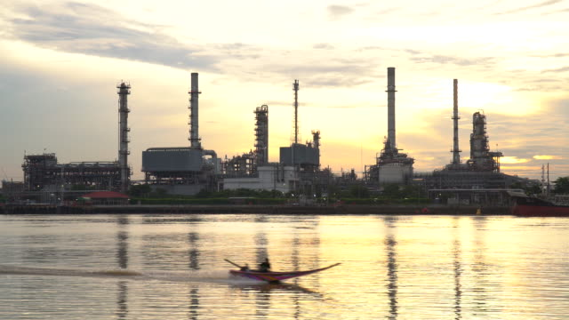 4k Oil refinery - petrochemical plant  at sunrise with reflection