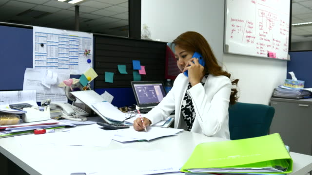 4K:Asian Businesswoman talking on the phone in Office