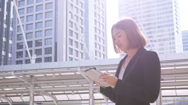 4K:Business woman using tablet in central of city