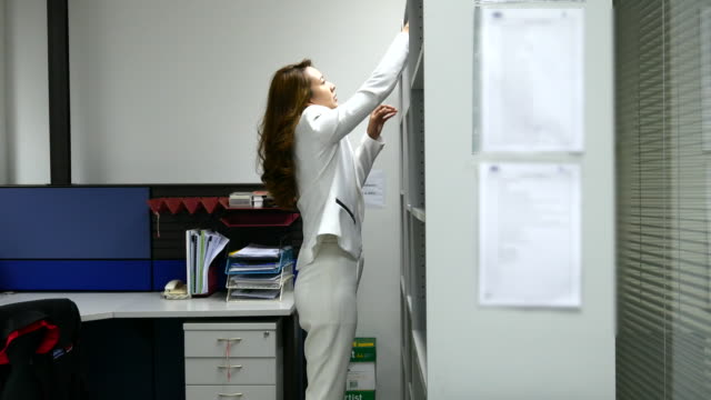 4K:Businesswoman finding document from cabinet and reading