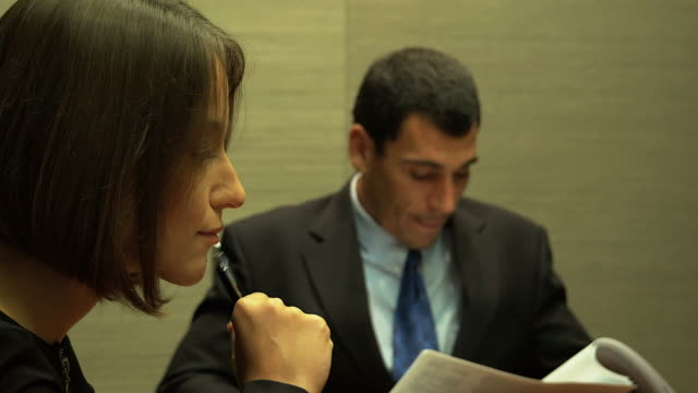 4K:Close-up of a serious businesswoman with colleagues in meeting.