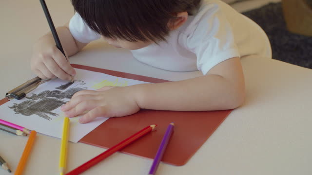 4K:Happy boy colouring in his room.