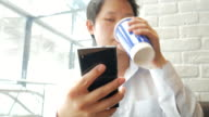 4K:Man Using on cellphone and drinking coffee in cafe