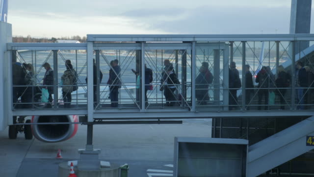 4K:Passengers leave the plane on gangway airplane