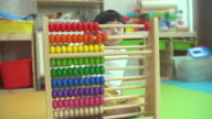 4K:Preschool baby boy learns to count. Cute child playing with abacus toy. Little boy having fun indoors at home.