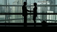 4K:Silhouettes of two business partners handshaking and greeting each other