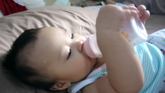 4K:Smiling baby  lying down while drinking milk from a bottle