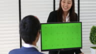 4K:two asian business people talking with computer green screen