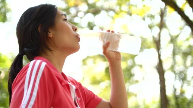 4K:Woman runner drinking water after race