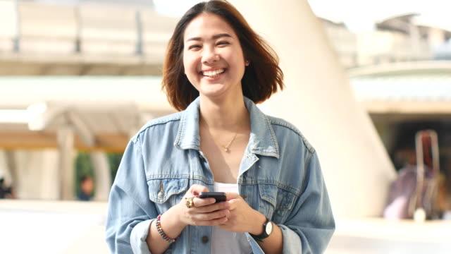 4K:Women smiling and using smart phone
