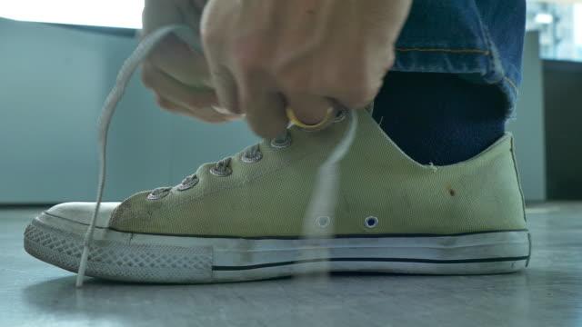 4k:Young Men tying shoelaces