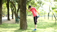 4K:Young woman leg stretching exercises in the Park