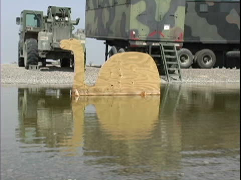 4th May 2005 MONTAGE Camel cardboard cutout in lake US soldiers engaging in horseplay / FOB Speicher Iraq / AUDIO